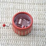Caja de música manual roja retro con melodías varias.